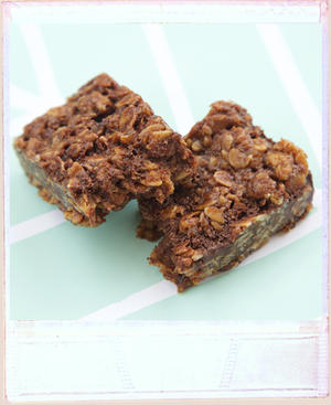 Soft baked chocolatey oat flapjack broken in half with its lovely texture on view