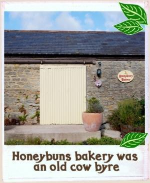 Honeybuns gluten free bakery housed in a converted cow byre, with a 'honeybuns Bakery' name plaque on the wall and plants in ceramic tubs.