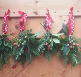 Festive pine tree decorations tied with red ribbon