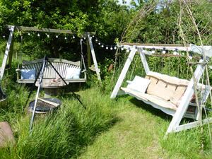 Two wooden swing benches in garden