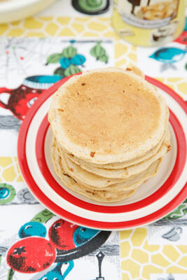Pile of small pancakes stacked on red rimmed plate on vintage tablecloth with Honeybuns cake mix in the backgorund