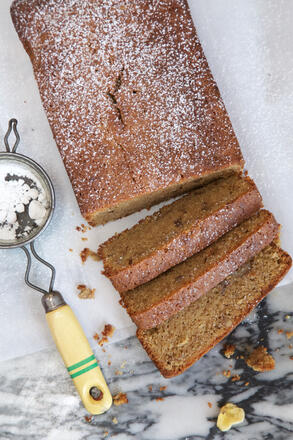 Slices of gluten free banana bread with icing sugar