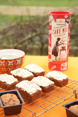 Gluten free and dairy free carrot cake loaves on cooling rack with cake mix in background
