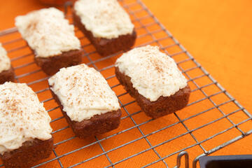 Mini gluten free and dairy free Carrot Cake loaves on wire rack and orange tablecloth