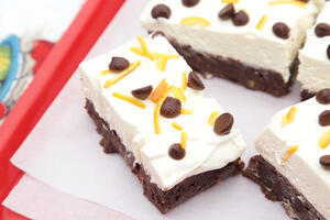 Gluten free chocolate brownie topped with vanilla cheesecake, on red tray