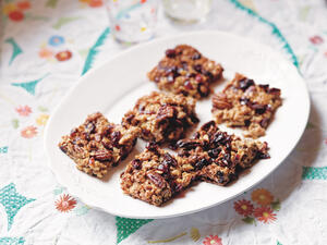 Cranberry, pecan and maple syrup flapjacks on plate