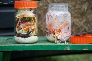 2 jars of layered coleslaw salad on a bench