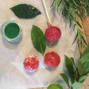Festive decoration of Glitter and jam in bowls with rosemary and bay sprigs
