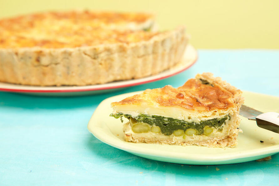 Early summer quiche with slice cut out