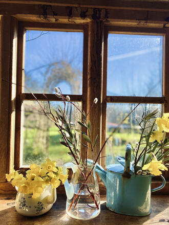 Easter floral decorations in vintage jugs on a window