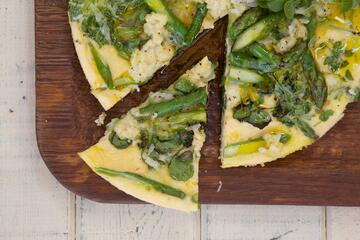 Frittata with asparagus and spinach topping on wood board