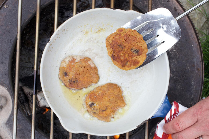 mini carrot pancakes cooking in pan over fire
