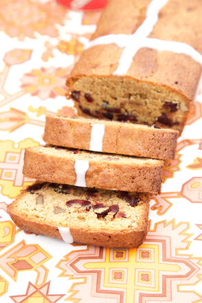 Sliced gluten free cranberry and orange cake on pink tablecloth