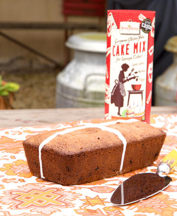 Gluten free cranberry and orange loaf cake with cake mix tube in background