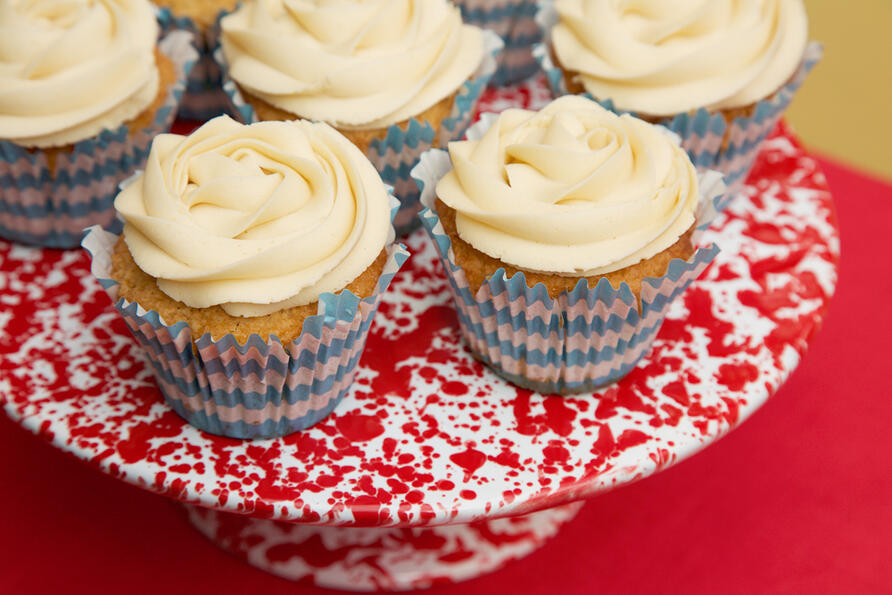 Pretty cupcakes with icing on top on an enamel cake stand