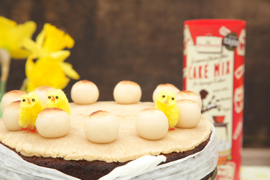 Gluten free Simnel cake with a layer of homemade marzipan and twelve marzipan balls, and stands on a vintage glass cake stand