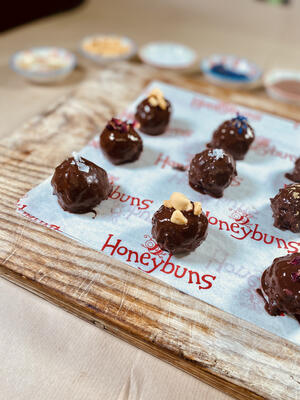 Homemade chocolate truffles lined up on wooden board