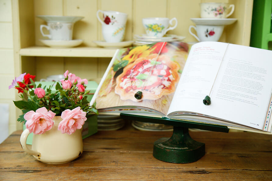 Cook book open on a book stand with vase of roses