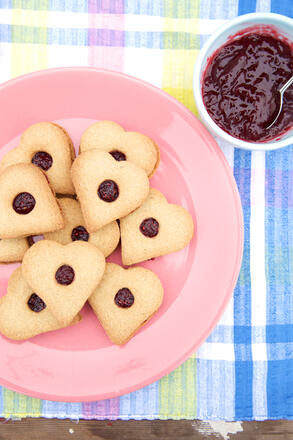 Gluten free heart shaped biscuits on pink plate with a bowl of jam