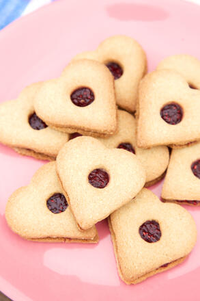 Heart shaped biscuits sandwiched with raspberry jam on pink plate