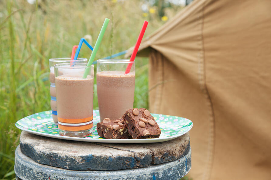 a summer scene of three chocolate milkshakes and milk chocolate brownies on a pretty tray in a meadow by vintage tent