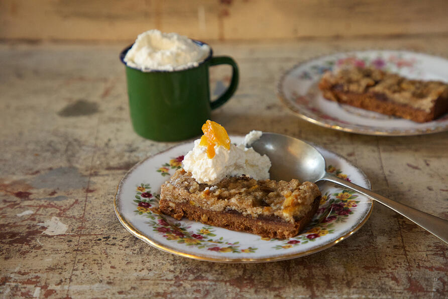 Mincemeat Cake slice on plate with cream and spoon served as a pudding