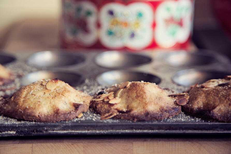 Gluten free mince pies in bun tin with vintage cake tin in background