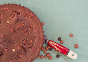 Chocolate tart with scattered hazelnuts