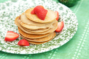 Pancakes and strawberries on green spot plate