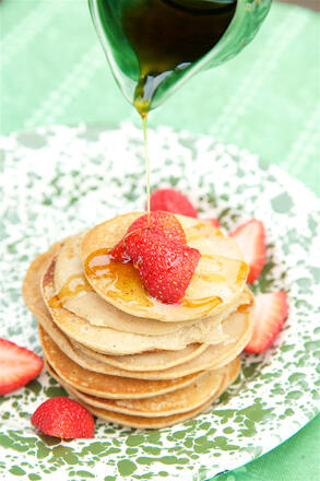 Pancakes with syrup and strawberries on plate