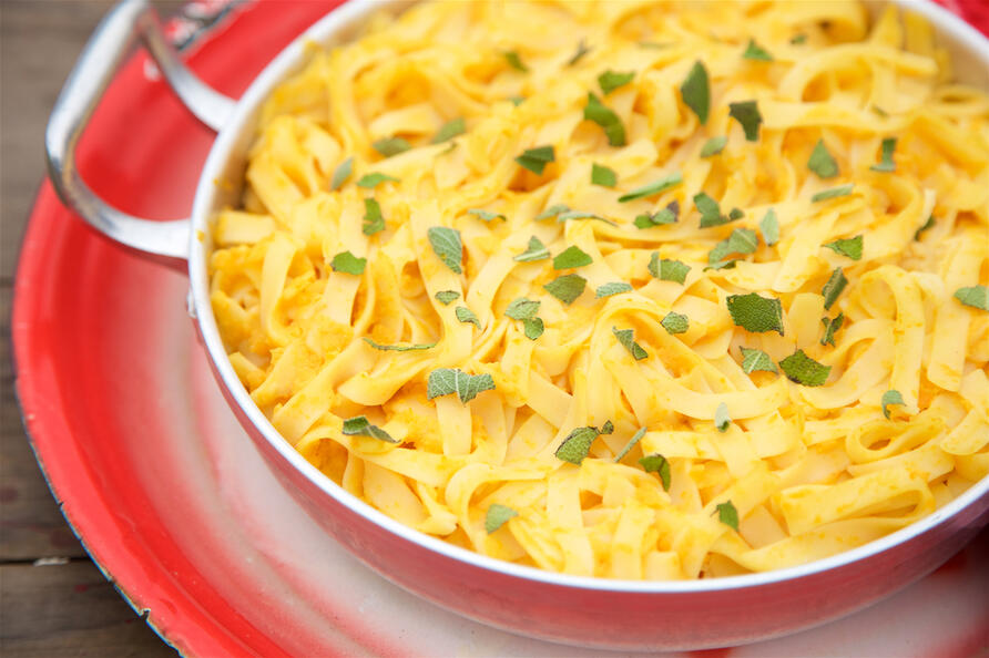 Bowl of gluten free pasta garnished with herbs and on a red tray