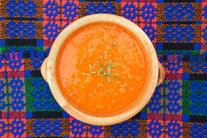 Gluten free roasted red pepper soup on blue mat