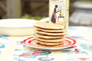 Pile of small pancakes stacked on red rimmed plate on vintage tablecloth with gluten free cake mix in the backgorund