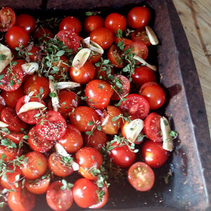 Roasting tin of garlic and cherry tomatoes