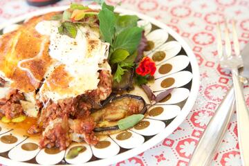 portion of moussaka on a plate with side salad