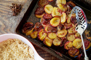 Roasted plum crumble bowl with stewed fruit and serving spoon