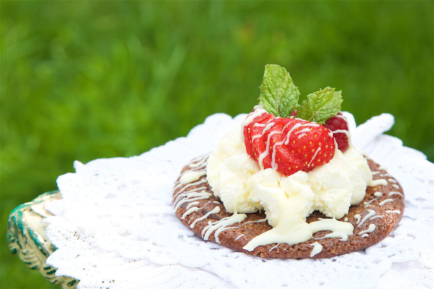 Chocolate cookie piled with cream, strawberries and a drizzle of chocolate on top, garnished with mint