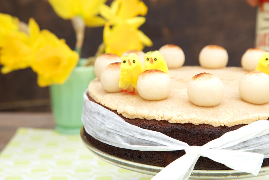 A gluten free sponge simnel cake decorated with marzipan and marzipan balls, on a vintage cake stand.