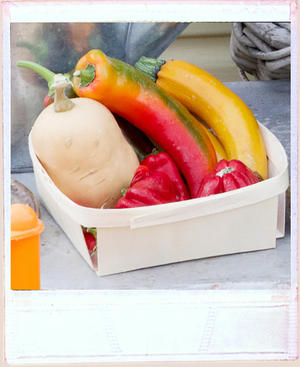Yellow courgette, red pepper and butternut squash on display in a wooden tray