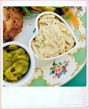 Homemade hummus in heart shaped dish, on a pretty vintage plate surrounded by sa;ad, pickle and a tart
