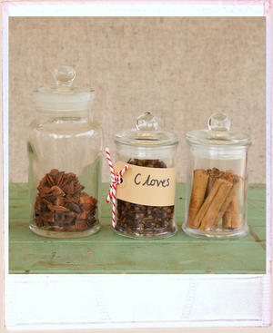 Three vintage glass jars lined up, one with cloves and lebelled with a hand written brown luggage tag, one with cinnamon in, and one with star anise in.