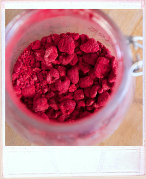 Overhead view into a glass kilner jar with freeze dried raspberries in it.