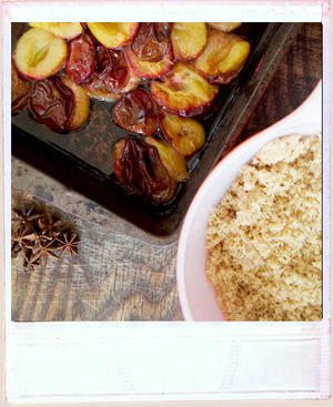 Roasted plums on a well worn chopping board, with star anise and a vintage dish with crumble in it