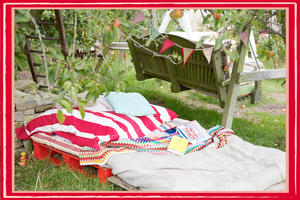 Pallet bed made up under an apple tree, with comfy cushions, blankets and bunting, open book and swing seat