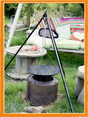 Wooden swing seats with colourful comfy cushions and blankets, a koptlich fire pit and large cable table.