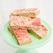 Oaty flapjack with raspberry puree stirred through and white vanilla topping bars piled on fabric