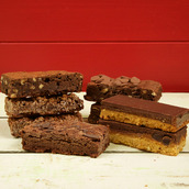 stack of chocolate cake slices including brownies and millionaire shortbread